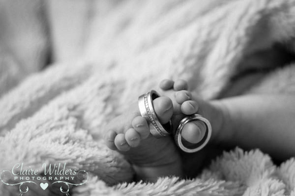a black and white photo of a newborn's feet with Mum & Dads wedding rings