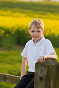Boy on fence, boy in rapeseed field, Horsham, rapeseed field
